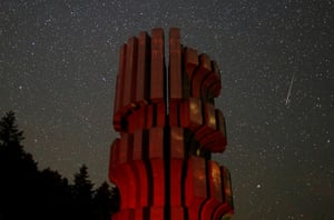 Prijedor, Bosnia and Herzegovina: A meteor streaks across the sky near the Monument to the Revolution, Kozara, during the peak of the Perseid meteor shower