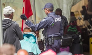 A Canadian police officer talks to migrants after they crossed the Canada-US border illegally near Hemmingford, Quebec