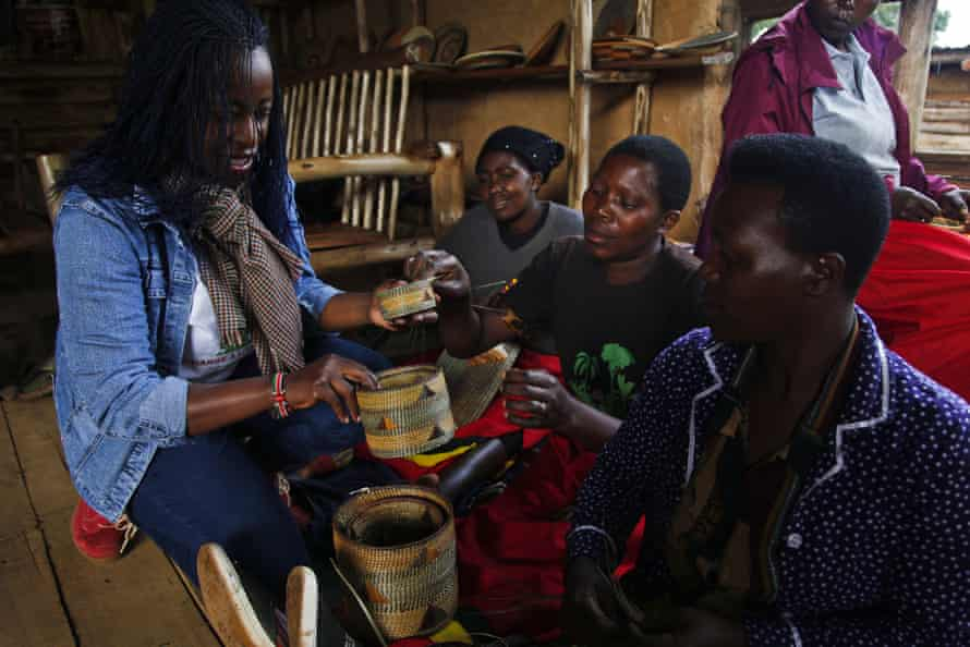 Tina Katushabe, left, sits with women supported by the Change A Life Bwindi charity as they weave colourful baskets.