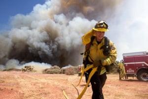A firefighter battles a brush fire
