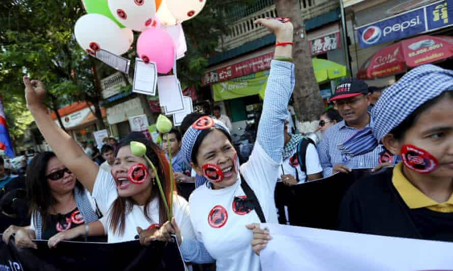 Women hold a banner as they shout during a protest against the new law to regulate non-governmental organisations in Phnom Penh, Cambodia, in July.<br>