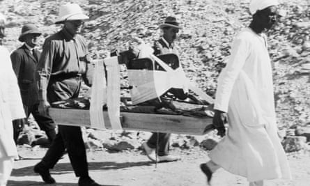 Egyptologist Howard Carter (centre) watches as porters carry a throne from King Tutankhamun's Tomb in the Valley of the Kings in Egypt, 1923.