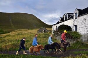 Jack, Penny, Sheila and Jim Grear walk their ponies to the ferry