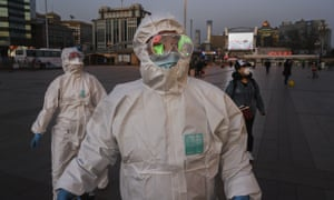 People wear protective masks and suits as they arrive at Beijing Railway Station on 13 March.