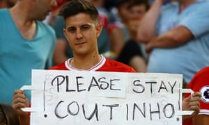 A Liverpool fan with a poster asking Philippe Coutinho to stay at the pre-season Audi Cup game against Atlético Madrid in Munich