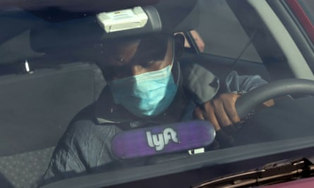 A Lyft driver wears a mask during the coronavirus outbreak, as he leaves passengers in the Capitol Hill neighborhood in Washington.