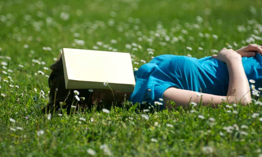 Student sleeping in the park with a book over her face