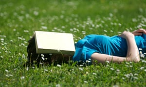A woman lying on some grass, sleeping with a book over her face