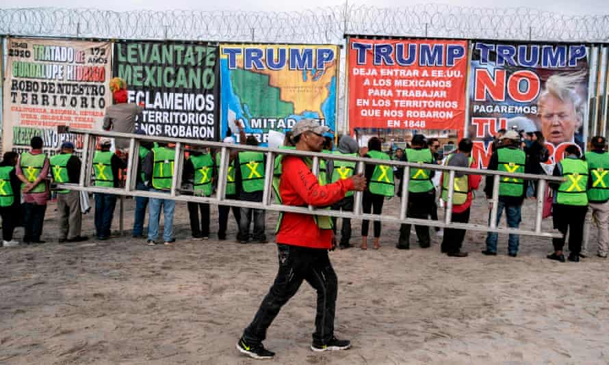 A man carries a ladder as members of Border Angels and Alianza Migrante (Migrant Alliance) look at banners during a demo against Donald Trump at the US-Mexico border in Playas de Tijuana, Baja California state, Mexico, on 2 February 2020.