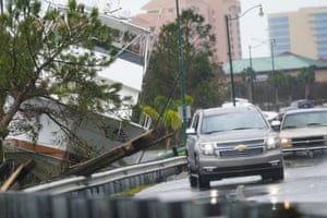 Vehicles maneuver on a flooded road near a boat washed up near the road in Orange Beach, Alabama.