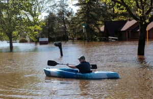 Joe Ryan paddles a kayak to check on his home in a flooded neighbourhood of Midland in Michigan, US, after the failure of two dams