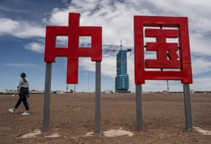 A woman walks by as the launch platform housing the Shenzhou-12 spacecraft and Long March-2F rocket is seen behind the Chinese characters meaning 'Zhongguo' or 'China' at the Jiuquan satellite launch centre