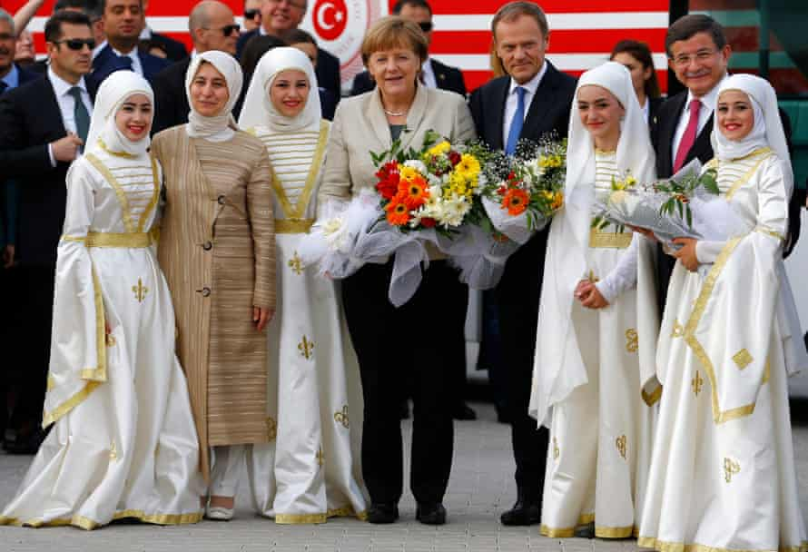 German chancellor Angela Merkel, EU council president Donald Tusk and Turkish prime minister Ahmet Davutoglu pose with refugees in traditional costume.