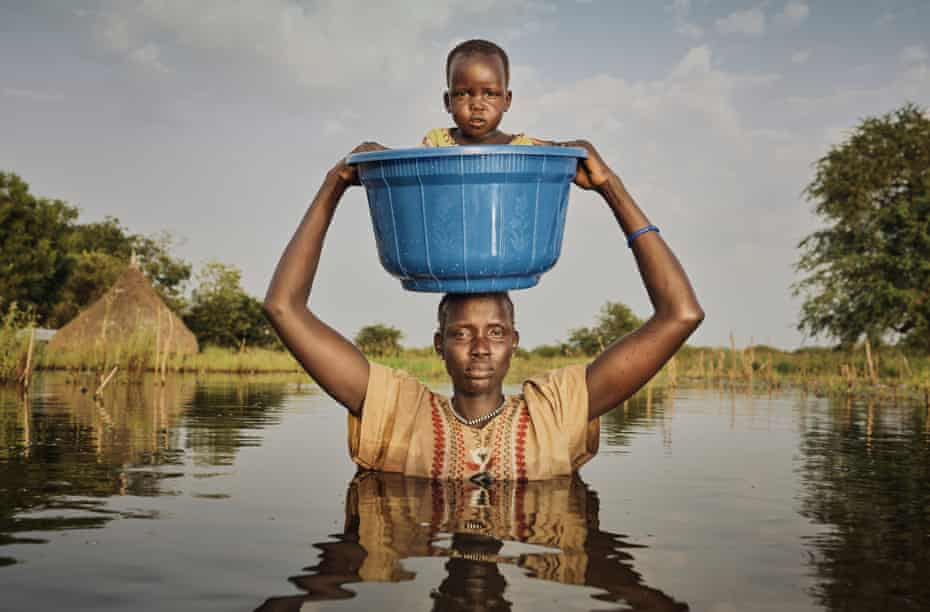 Nyalong Wal, 36, carries her daughter Nyamal Tuoch, 2, to dry land
