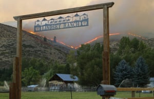 Flames and smoke rise on a ridge line above a ranch on Twisp River Road