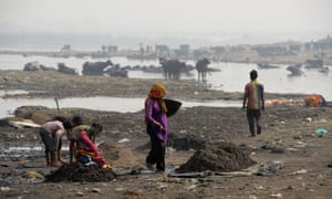 People work on the banks of Ramganga river as they collect scrap metal left as waste by brass factories in Moradabad.