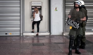 A woman withdraws €50 from a cash machine in Athens. But for how long will Greek banks have enough cash to dispense?
