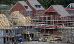 Houses under construction with scaffolding and boards outside