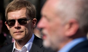 Britain's Labour Party's Executive Director of Strategy and Communications Seumas Milne (L) watches as British Labour party Leader Jeremy Corbyn gives a television interview outside the Houses of Parliament