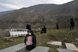 Relatives of a man who died from Covid-19 mourn at a cemetery on the outskirts of the city of Ghaemshahr.
