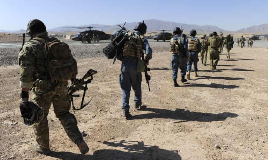 Afghan officers and Australian soldiers walk towards a Black Hawk helicopter in Kandahar