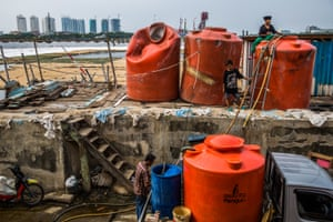Residents fill up a water tank with clean water