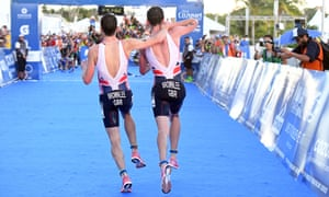 Britain's Alistair Brownlee, right, helps his brother Jonny to get to the finish line during the Triathlon World Series event in Cozumel Mexico