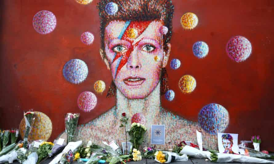Flowers lie in front of a mural tribute to Bowie in Brixton, London, after his death in January 2016.
