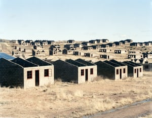 Incomplete houses, part of a stalled municipal development of 1,000 houses. The funding allocation was made in 1998, building started in 2003. Officials and a politician gave various reasons for the stalling of the scheme: shortage of water, theft of materials, problems with sewage disposal, problems caused by the high clay content of the soil and the shortage of funds. By August 2006, 420 houses had been completed. Lady Grey, Eastern Cape, 5 August 2006. From the series Intersections (detail), 2006