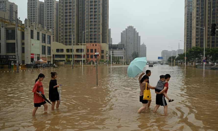 People wade across a flooded street in the city of Zhengzhou in China's Henan province.