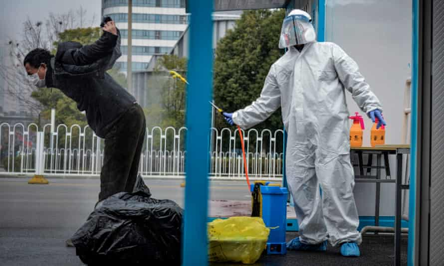 A man who recovered from Covid-19 is disinfected by medical staff as he leaves a hospital in Wuhan, China, in February 2020.