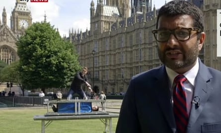 The faked news report shows two magicians rolling their equipment into background of the shot and performing an illusion as Joshi reports on the government's NHS plans.