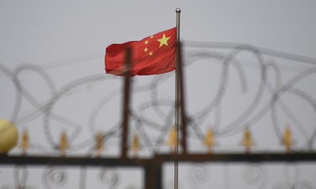 A Chinese flag behind razor wire at a housing compound in Yangisar, south of Kashgar, in China's western Xinjiang region