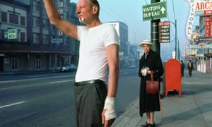 Man With bandage, 1968, by Fred Herzog. The man seems to be hailing an approaching bus, while an elderly woman looks on quizzically, keeping her distance. The image is almost Hitchcockian.