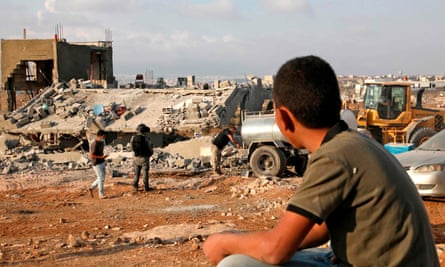 A Palestinian boy watches as Israeli machinery demolishes a house near the Palestinian village of Yatta in the West Bank on 2 November 2020.