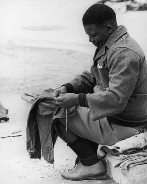 Nelson Mandela sewing prison clothes in the yard of Robben Island prison off Cape Town, 1966