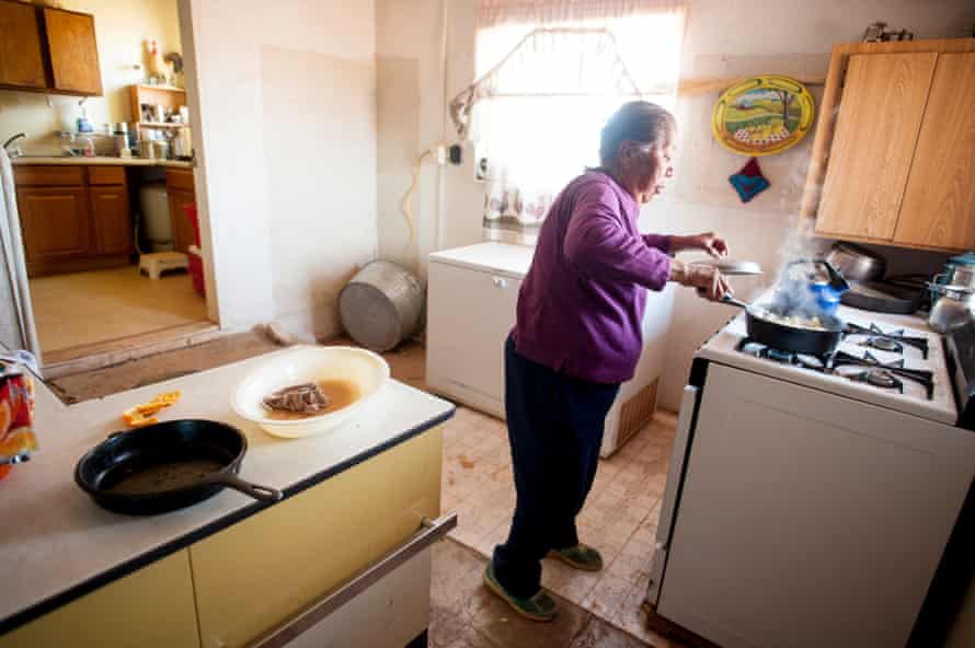 Eleanor Peshlakai prepares dinner in her home on the Navajo Nation reservation in Black Falls, Arizona.
