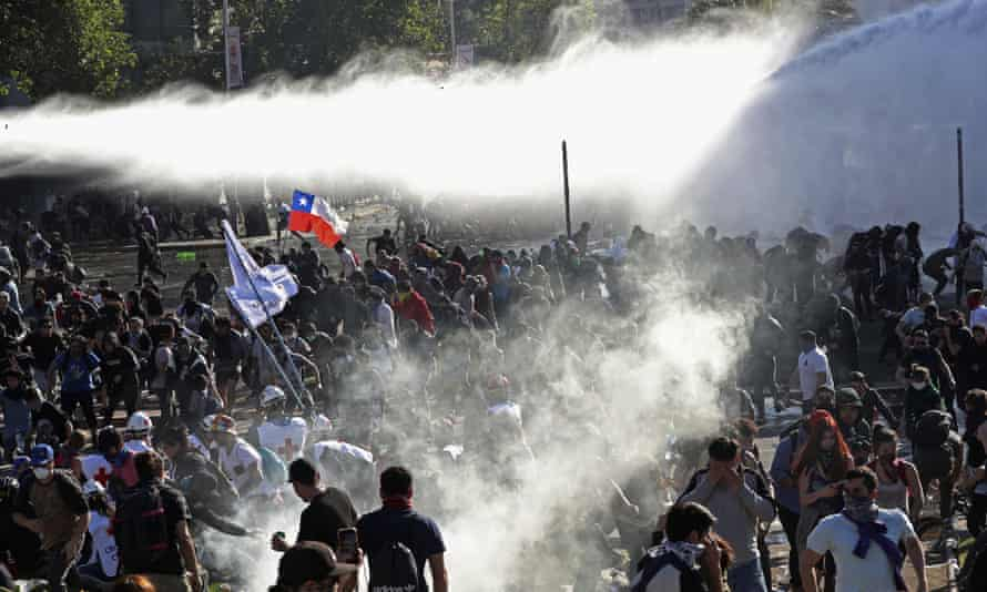 Demonstrators run from police firing water cannon and teargas in Santiago