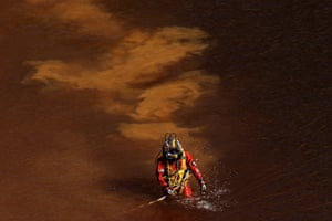 A diver walks out from a toxic man-made lake after a search for a third victim, part of an investigation hunting for bodies dumped by a suspected serial killer