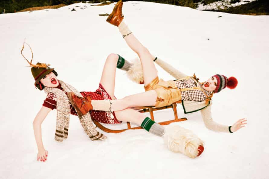 Two women falling off a sledge on the snow dressed colourfully in shorts, bobble hat and scarf