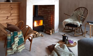 A rocking chair with a fleece on it and a reclined chair with a cushion and throw, either side of a fireplace with a lit log-burning stove