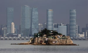 Photograph of a very small island with a few homes on it against a background of Xiamen's skyscrapers