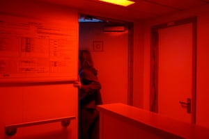Volunteer deckhand Luca Lamont enters the bridge of the ship during her early morning watch shift from 4am to 8am. At night the lights in the alleyway turn red as it does not impair their night vision as much as normal lights. This makes their job easier as they can quickly shift from red light inside to darkness outside without waiting for their eyes to readjust
