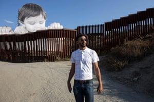 El artista francés JR representó cerca de sus ilustraciones en la frontera de los EEUU-México en Tecate, California, los EEUU.