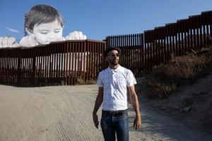 French artist JR pictured near his artwork on the US-Mexico border in Tecate, California, USA.