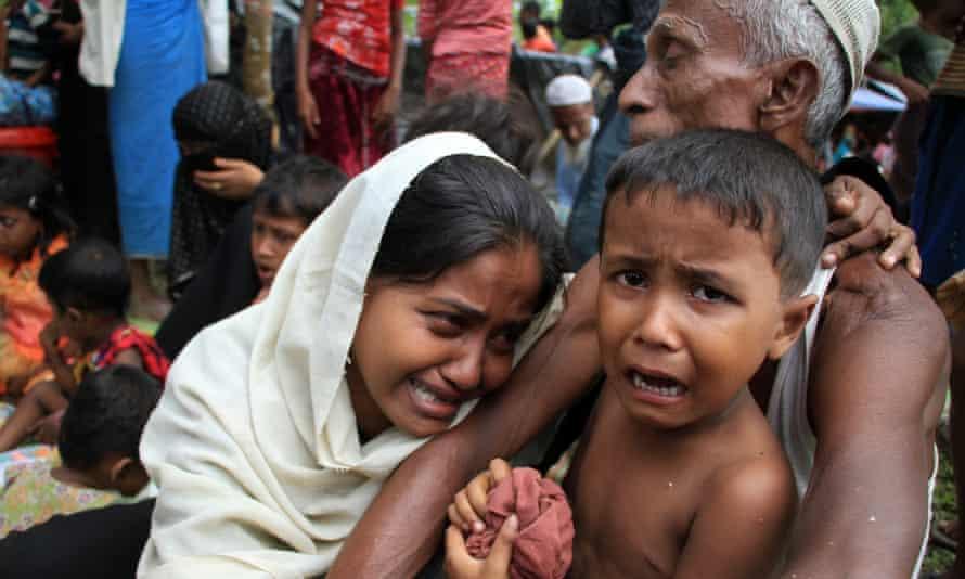 Rohingya refugees crying at a makeshift shelter at the border village of Gumdhum.