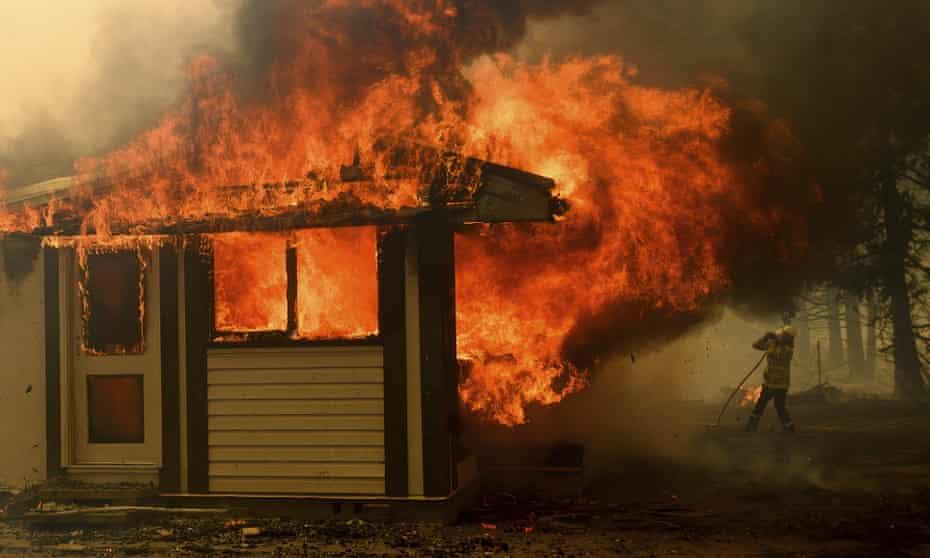 A firefighter battles a fire consuming a home near Bundanoon, New South Wales.