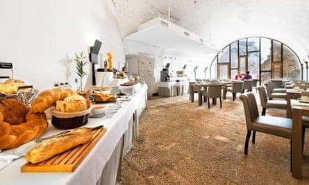 White-walled dining area, with bread on a large table at Domus Real Fuerte de la Concepción in Aldea del Obispo, Salamanca.