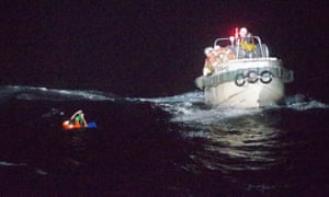 A Filipino crew member of a Panamanian ship carrying thousands of cows is rescued by the Japanese coast guard members near Amami Ōshima island last month.