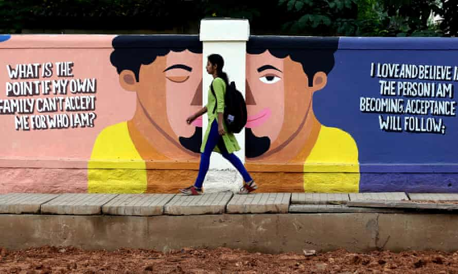 A woman walks past a painting to raise mental health awareness on a wall in Bangalore, India, in September 2019.